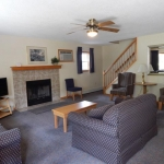 2,000 sq. ft. townhouse with 4 bedrooms - Living area with couch, fireplace, and stairs