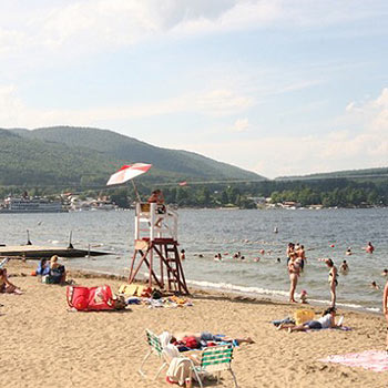 Photo of the beach with people swimming in the water